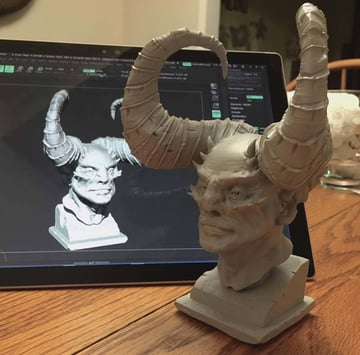 A 3D printed demon bust with the 3D model displayed in the background.