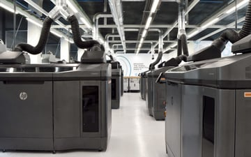 Print farm of industrial scale 3D printers.