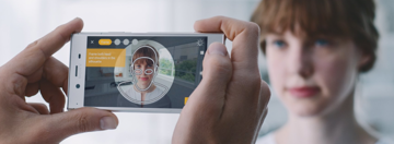 Scanning a boy's face with a smartphone.