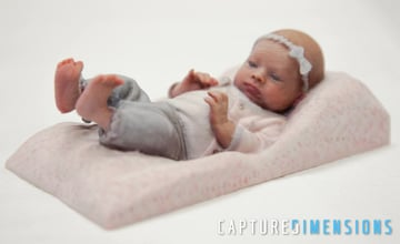 A 3D printed model of a baby sleeping, bow and all.