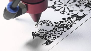 Beautiful patterns laser cut into into card stock paper.
