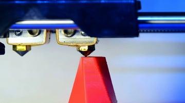 A 3D printer hard at work drooling plastic.