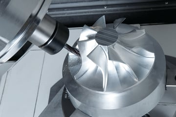 A metal part being machined on a 5-axis mill.