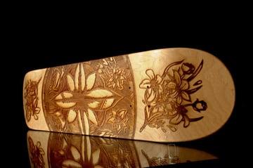 Laser-engraved design on a wood skateboard.
