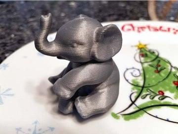 A sitting elephant in silky grey.