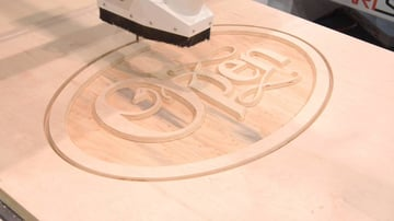 CNC milling a simple 2D design into a wooden plank.