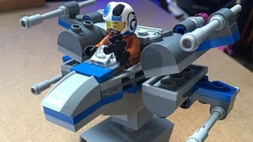 A mini Lego X-Wing with stand