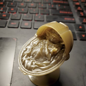 A resin print of Baby Yoda in his crib