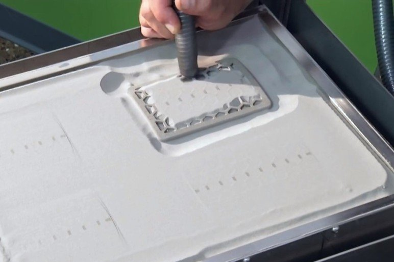 Removing the excess powder from a binder jet print.