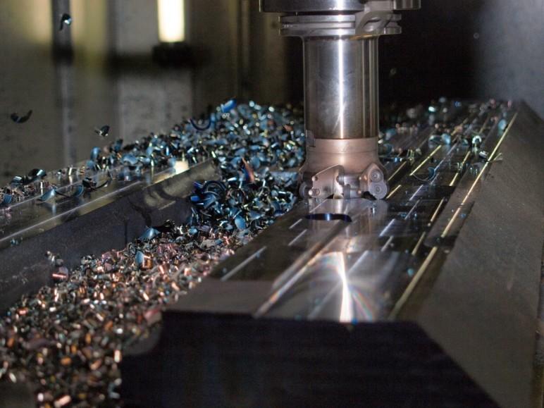 A CNC machine removes metal.
