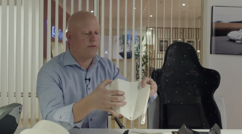 Koenigsegg's CEO holding a 3D printed prototype for the leg rest
