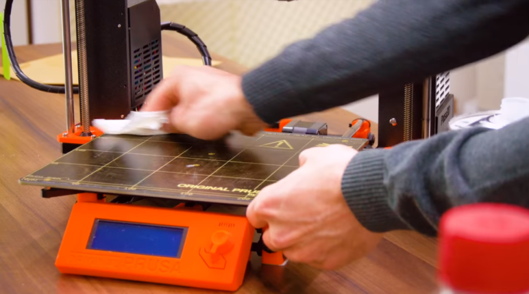 A user cleaning the print bed of a 3D printer.