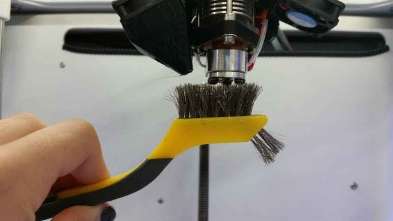 How to clean a 3D printer nozzle using a brush.