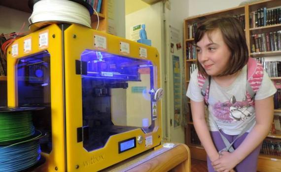 A youngster eagerly waits for her 3D project to print at a public library.