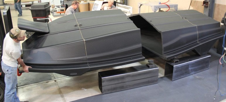 Gluing pieces of a life-size 3D printed boat hull.