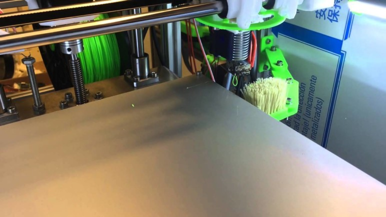 Brush mounted on the side of the bed. G-code can be used to make the hot end wipe off any residue prior to printing.