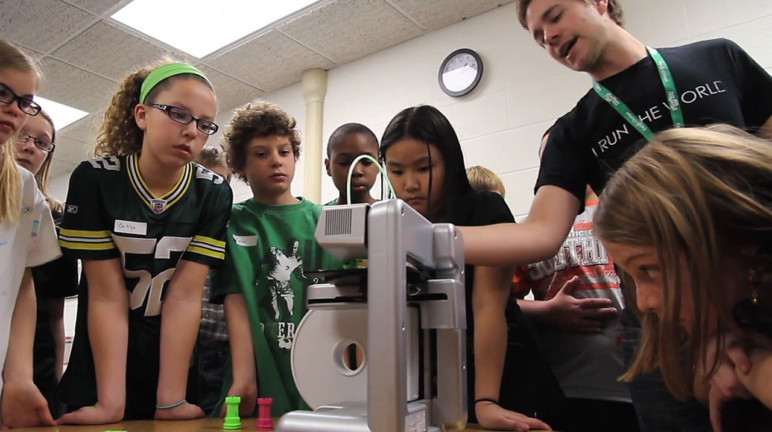 A teacher showing kids how 3D printing works.