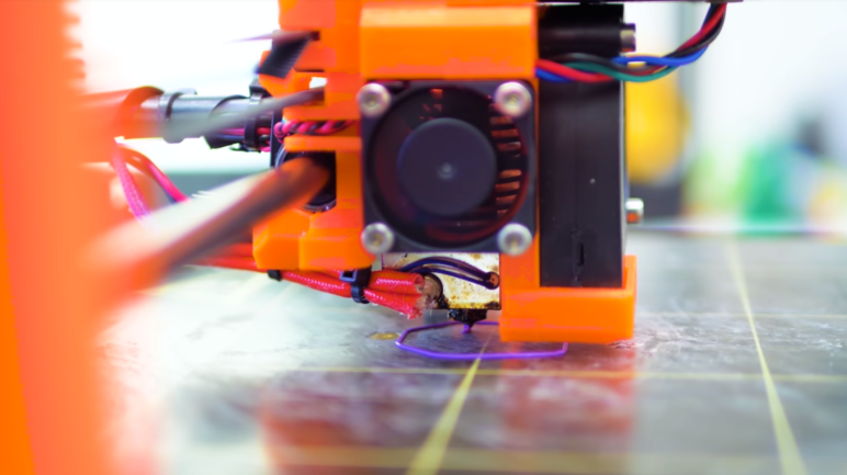 3D printer extruding the first layer onto a print bed.