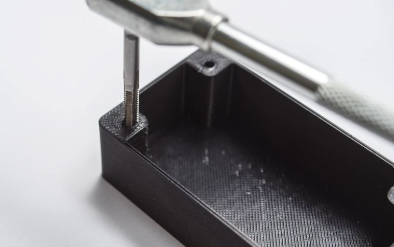 Cutting a thread with a tap wrench.